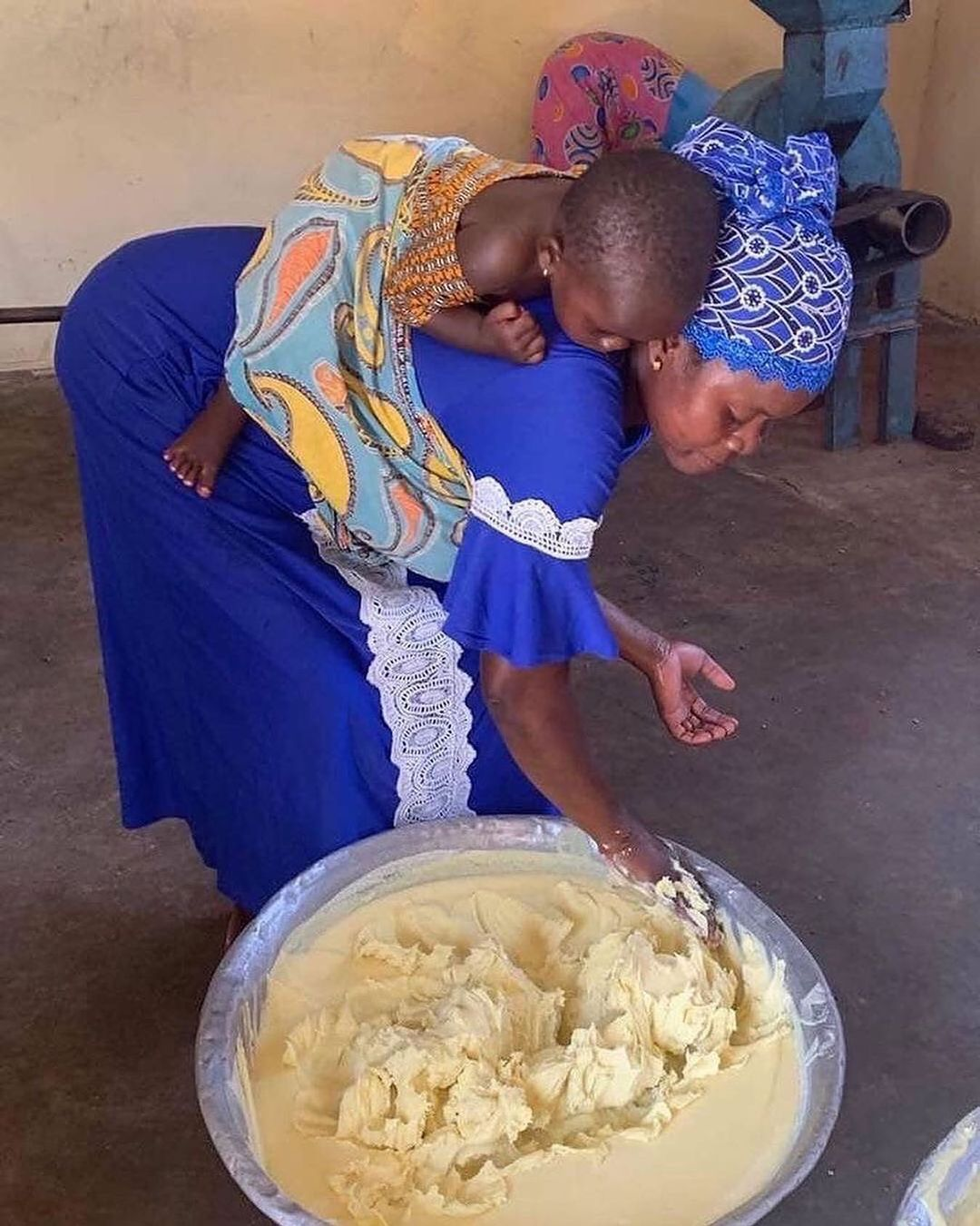 woman making shea with her child on her back